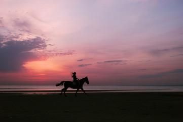 Woman riding horse along shore