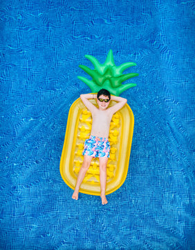 Little boy lying on a pineapple-shaped float in a swimming pool
