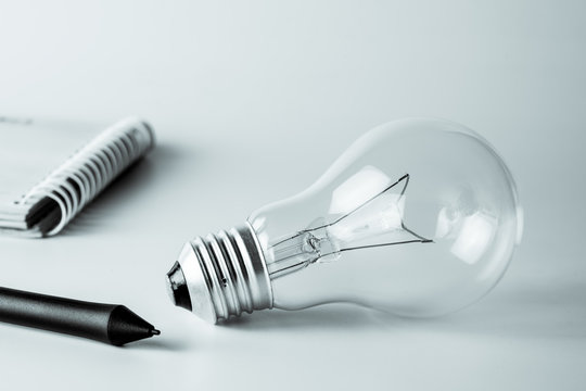 New Idea Concept with Light bulbs, pen and open spiral notebook, Black and white image.