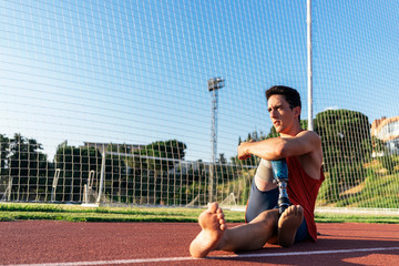 Disabled man athlete stretching with leg prosthesis
