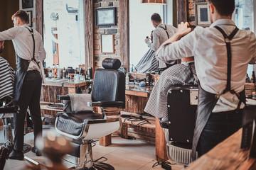 Thendy focused hairdresser at modern barbershop is working on client's haircut. Fotoväggar
