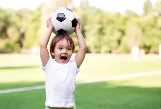 Excited little toddler boy playing football on soccer field outdoors: the kid is holding ball above head and shouting ready to throw it. Active childhood and sports passion concept