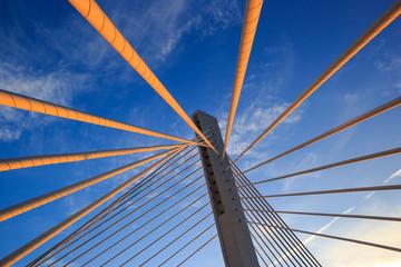 Fototapeta premium Kable wychodzące z kolumny mostu wantowego pod lekko zachmurzonym błękitnym niebem w słoneczny dzień. Most milenijny o zachodzie słońca w Podgoricy, Czarnogóra.