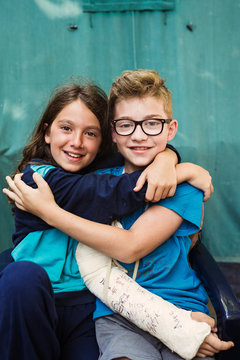 Sister embrace her brother with broken arm