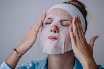 Young woman applying textile mask on her face