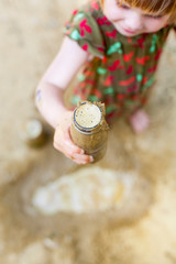 Kind spielt mit matsch - Kleines Kind hält Flasche mit Matsch. Kid playing with mud - holding bottle with mud