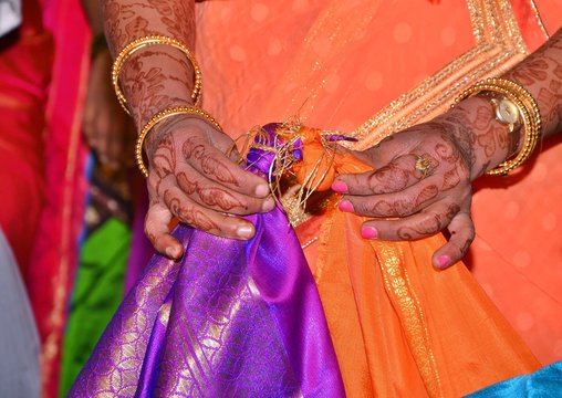 Maharashtrian Wedding Ritual - Gathbandan - Brides sister tying knot of Bride and Grooms clothes.The couple walks around the fire, the bride leading, and take solemn vows of loyalty, steadfast love