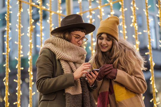 Young Women Using A Phone On The Street With Christmas Decoration Behind Them