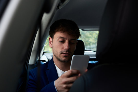 Dark portrait of smart casual businessman inside of taxi.