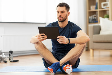 sport, fitness and healthy lifestyle concept - man with tablet computer sitting on exercise mat at...