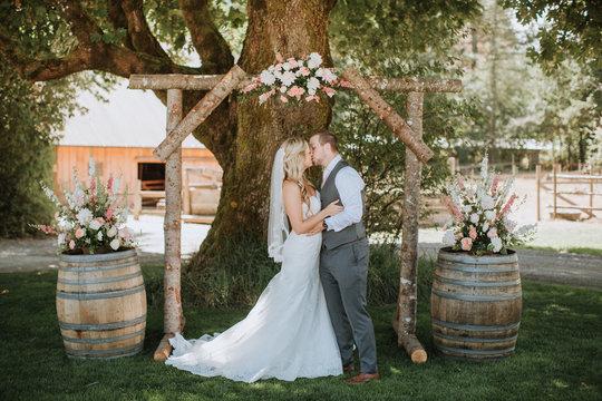 Wedding Couple Kissing under Arbor