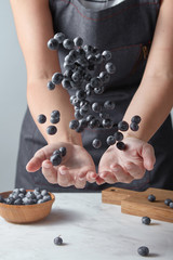 Midsection of woman tossing blueberries