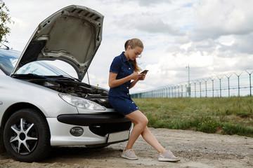 Woman using smartphone at broken car