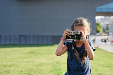 Small kid with film camera and braids at park.