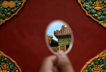 Children look at ancient buildings with mirrors. in China
