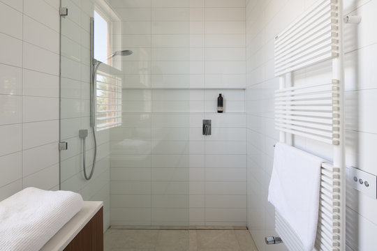 White tiles shower with heated towel rail