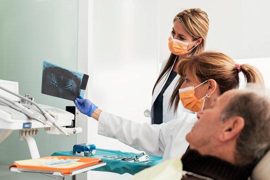 Dentist during a dental intervention to senior man