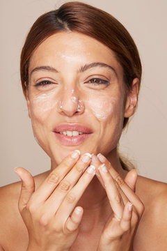 Woman portrait applying cream or moisturiser isolated In studio - skin care hydration closeup