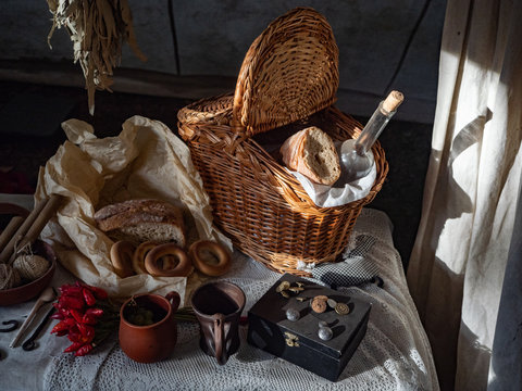 Still life. Wicker basket with fresh bread and a bottle of water, bay leaf, hot pepper and different tinsel on a wooden table with tablecloth