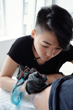 Young woman artist making tattoo