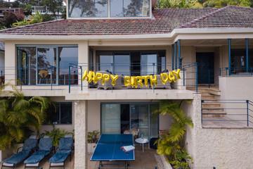 happy birthday balloon sign on house