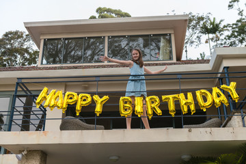 young teen posing with happy birthday sign