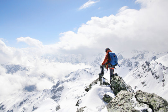 mountaineer on the top of a mountain in the background of the landscape of snowy mountains