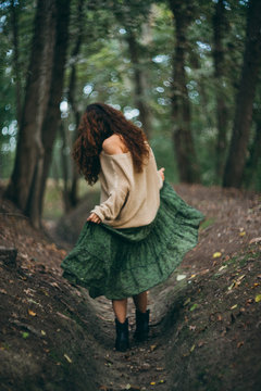 woman walking and dancing in the forest with dress