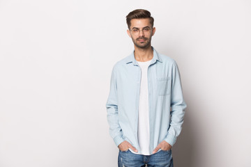 Serious millennial guy wearing glasses casual clothes posing studio shot
