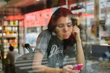 Young woman listening to music in bodega