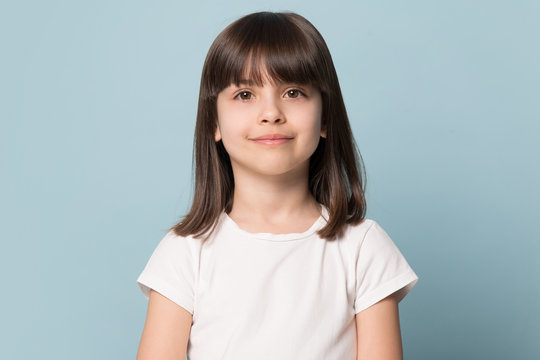 Little girl looking at camera isolated on blue studio background
