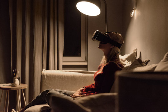 Chilling woman in VR headset sitting on couch
