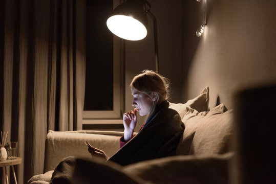 Woman having chips while using tablet on sofa