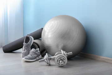 Set of sports equipment with fitness ball and shoes near color wall