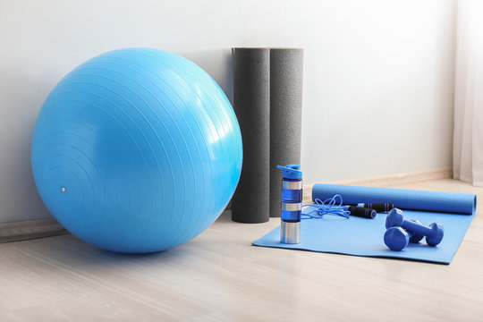 Set of sports equipment with fitness ball and bottle of water near light wall