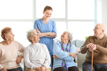 Young caregiver with group of senior people in nursing home
