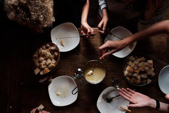 group of teen eating cheese fondue