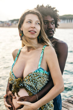 Beautiful Multicultural Couple Holding Woman's Pregnant Belly On The Beach