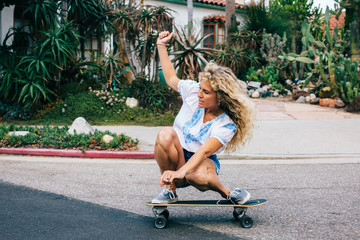 Athletic Young Woman Skateboarding Fast in Venice Street