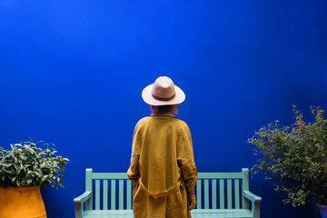 Woman In Hat  Stands By Blue Wall