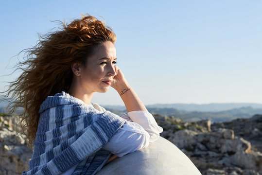 Outdoors portrait of woman watching sunset.