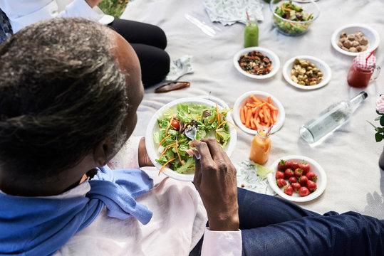 Senior black male eating salad at picnic. Anonymus overhead.