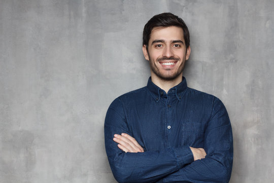 Portrait of young European male in denim shirt looking at camera with confident smile, isolated on gray background