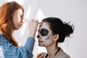 Make up artist creating stylish make up for halloween