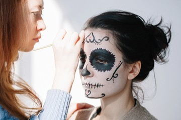 Make up artist working on skull make up for halloween