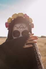 Woman with halloween make up hiding half of her face
