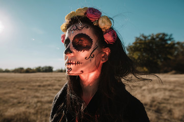 Halloween portrait of woman with scull make up  in bright unusual light