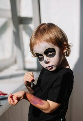Creepy little boy with face art of skeleton painting on his own hand
