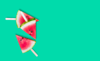 three slices of watermelon on green background with sticks