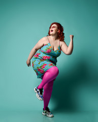 Funny plus-size lady overweight woman in fashion sunglasses and sundress running from something and laughing loud on mint